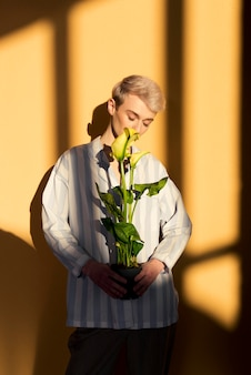 Medium shot model met bloemen en gouden licht