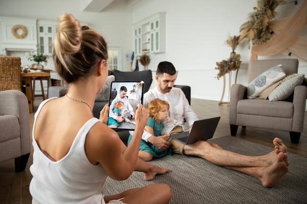Medium shot moeder die foto's maakt van familie