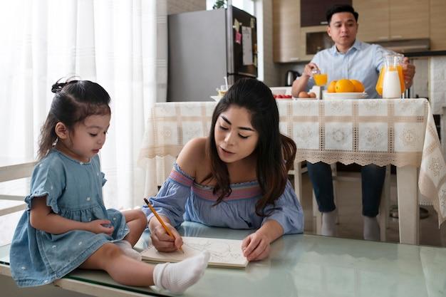 Medium shot moeder die op papier tekent