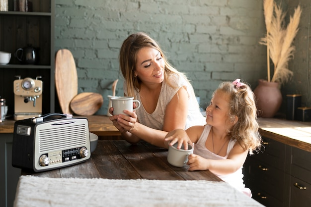 Medium shot moeder en dochter bekers houden