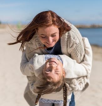Medium shot moeder en meisje spelen