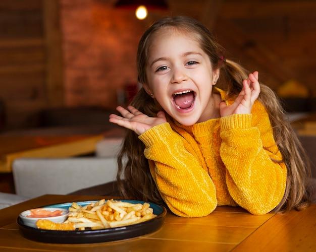 Medium shot opgewonden meisje met eten