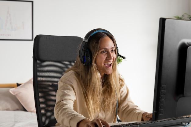 Medium shot opgewonden vrouw die op de computer speelt
