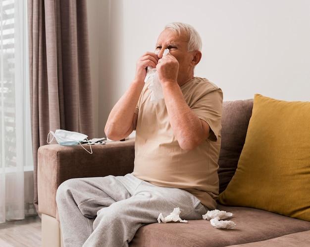 Medium shot oude man snuit zijn neus