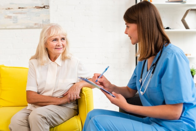 Medium shot oude vrouw en verzorger praten