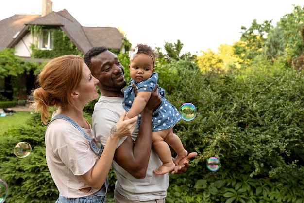 Medium shot ouders die baby vasthouden