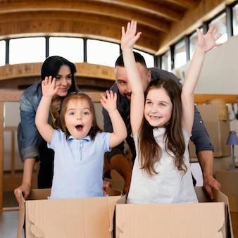 Medium shot ouders en kinderen met dozen