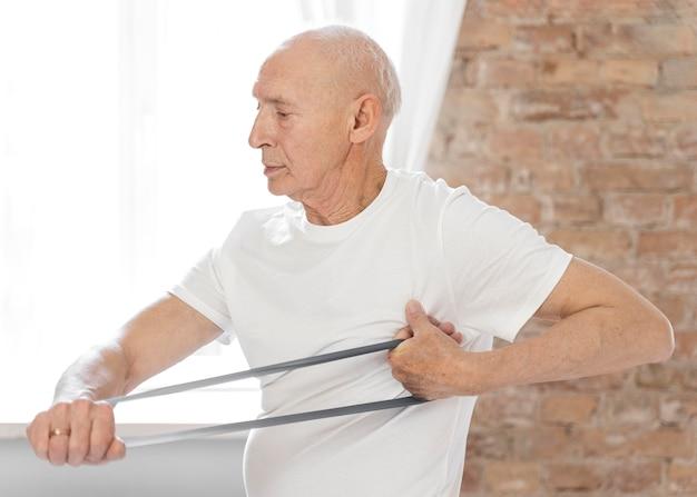 Medium shot senior man met elastische band