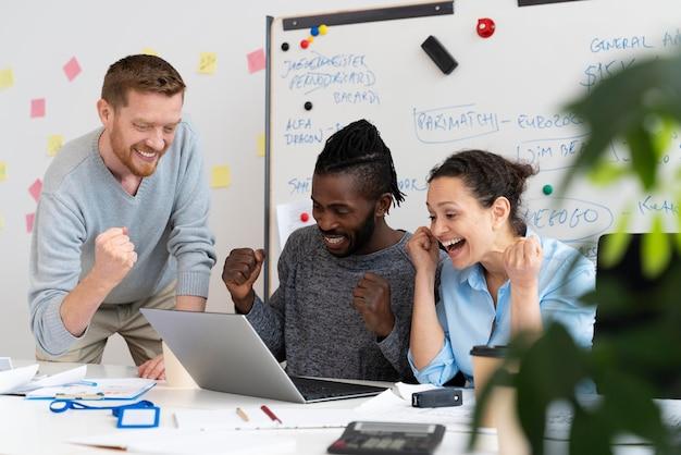Medium shot smiley collega's met laptop