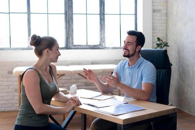 Medium shot smiley dokter in gesprek met vrouw