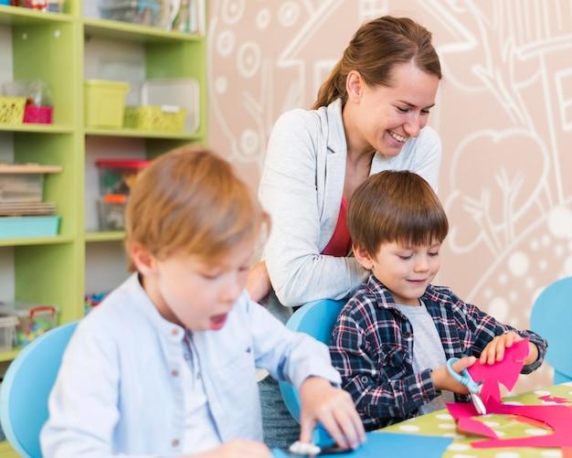 Medium shot smiley leraar die naar kinderen kijkt