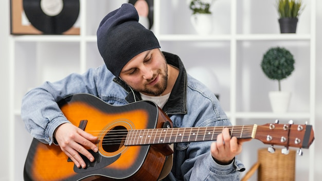 Medium shot smiley man gitaar spelen