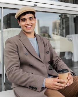 Medium shot smiley man met koffie Gratis Foto