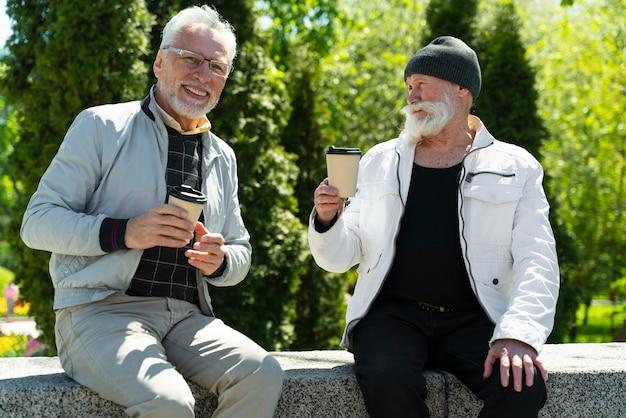 Medium shot smiley mannen met koffiekopjes