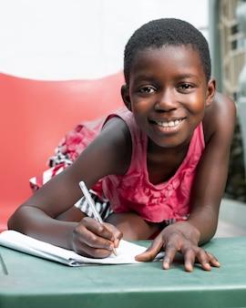 Medium shot smiley meisje dat op notitieboekje schrijft