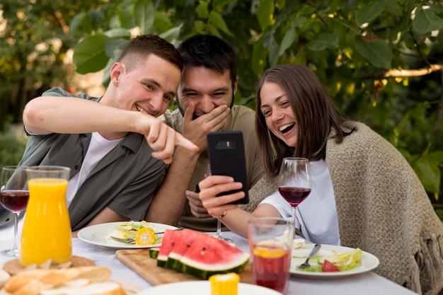 Medium shot smiley-vrienden die naar de telefoon kijken