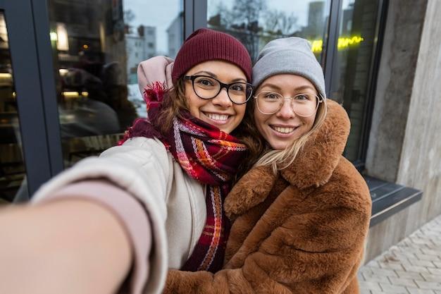 Medium shot smiley vrienden die selfies maken