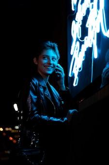 Medium shot smiley vrouw en neonlicht
