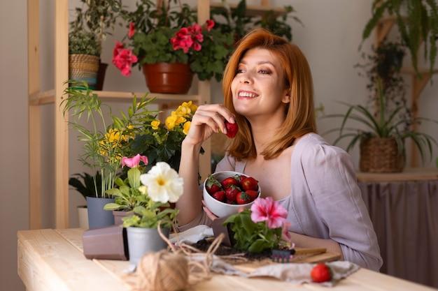 Medium shot smiley vrouw met fruit en bloemen