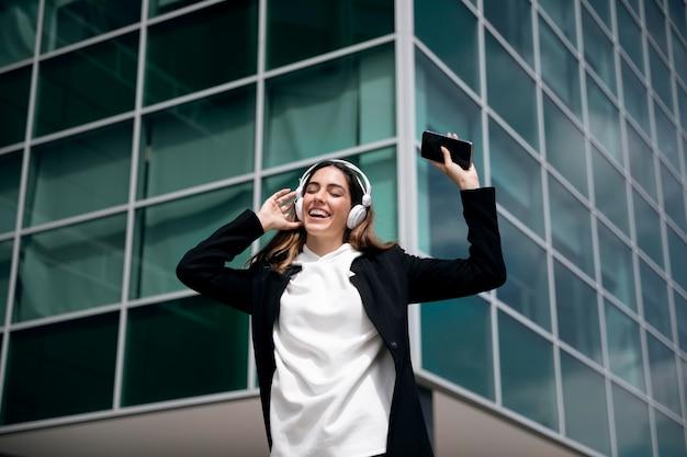 Medium shot smiley vrouw met koptelefoon Gratis Foto