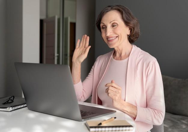Medium shot smiley vrouw met laptop