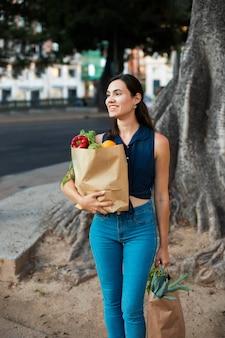 Medium shot smiley vrouw met papieren zak