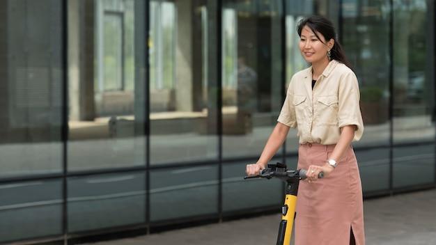 Medium shot smiley vrouw met scooter