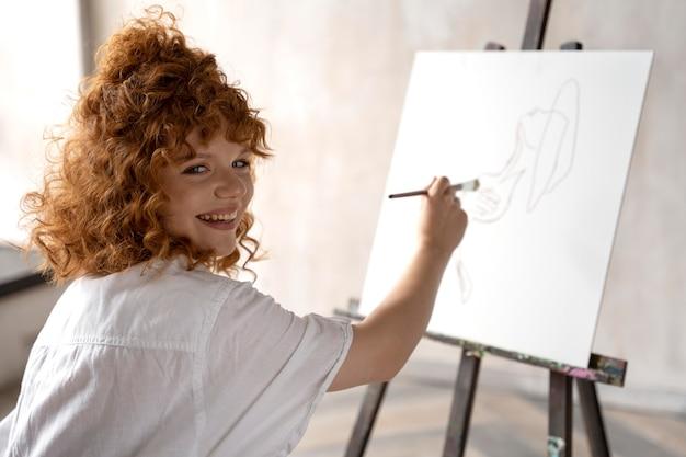 Medium shot smiley vrouw schilderen op canvas