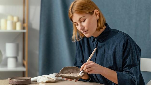 Medium shot smiley vrouw schilderij blad