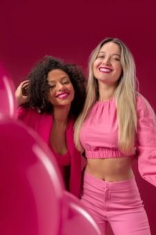 Medium shot smiley vrouwen met roze ballonnen