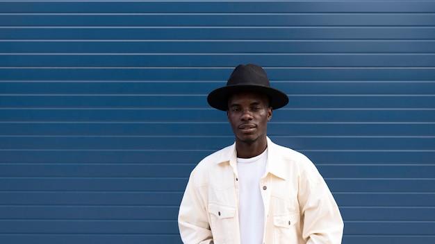 Medium shot smileyjongen poseren met hoed