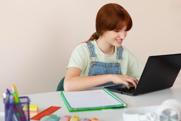 Medium shot smileymeisje typen op laptop