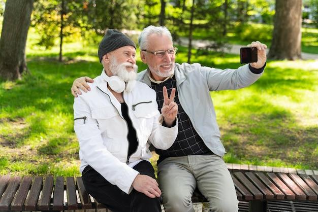 Medium shot smileyvrienden die selfies maken