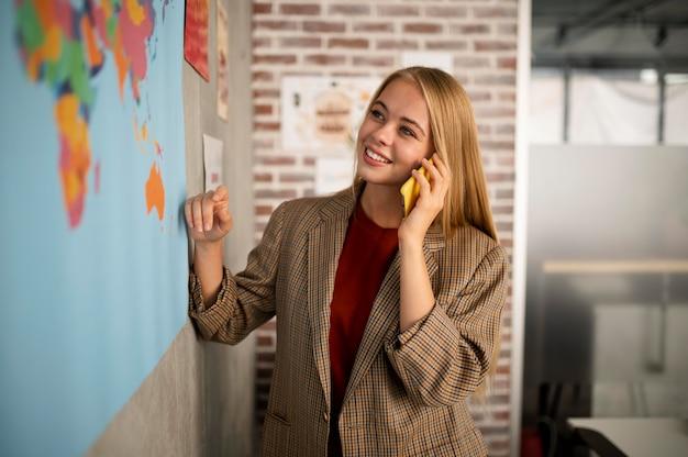 Medium shot smileyvrouw die aan de telefoon praat