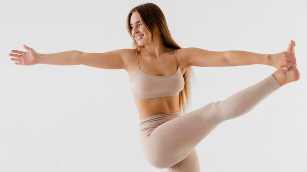 Medium shot smileyvrouw die haar been vasthoudt