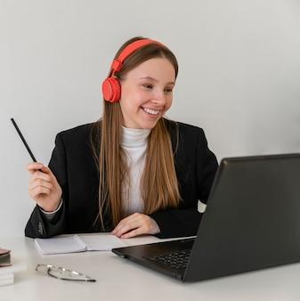 Medium shot smileyvrouw die met laptop werkt