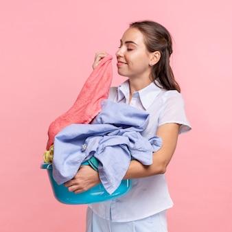 Medium shot smileyvrouw die schone kleren ruikt