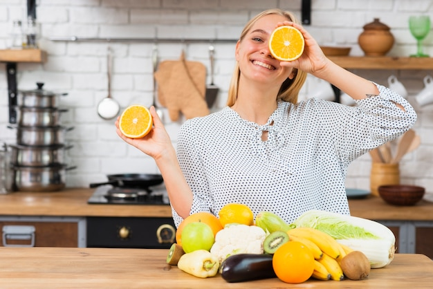 Medium shot smileyvrouw spelen met sinaasappels