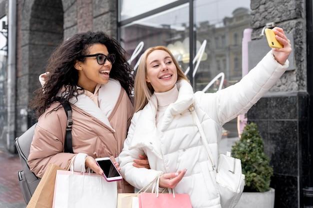 Medium shot smileyvrouwen die selfie maken