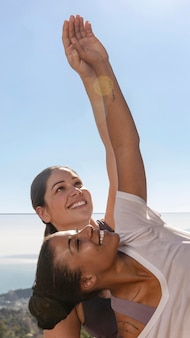 Medium shot smileyvrouwen die yoga doen