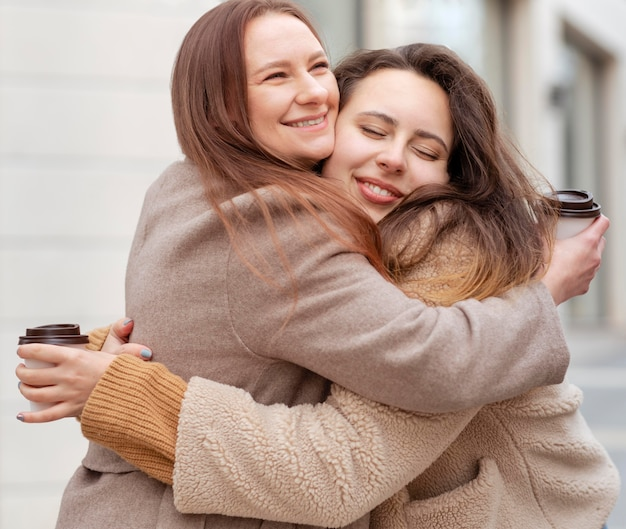 Medium shot smileyvrouwen knuffelen