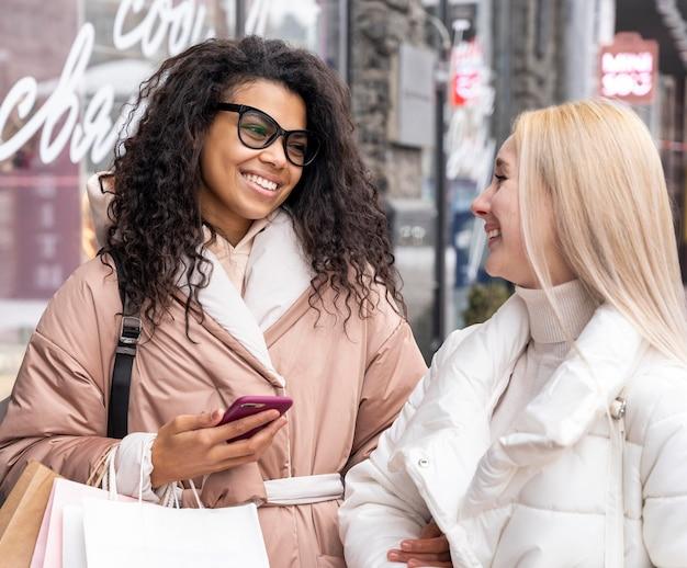 Medium shot smileyvrouwen met telefoon