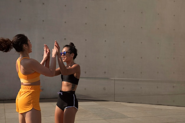 Medium shot sportieve vrouwen high five