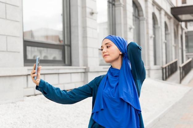 Medium shot tienermeisje dat een selfie neemt