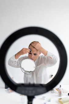 Medium shot transgender die make-up aanbrengt