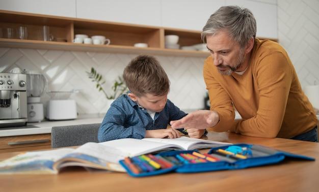 Medium shot vader en kind huiswerk