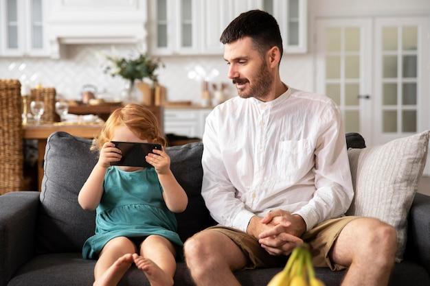 Medium shot vader en kind met apparaat