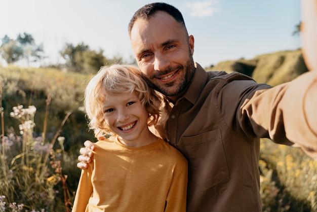 Medium shot vader en kind nemen selfie