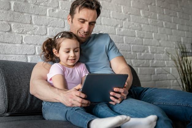 Medium shot vader en meisje met tablet