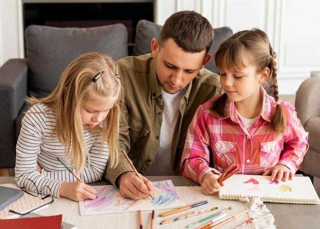 Medium shot vader en meisjes tekenen